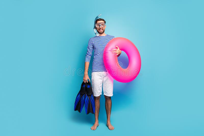Full body photo of funny excited guy tourist swimmer hold underwater mask breathing tube flippers pink lifebuoy wear stock photos