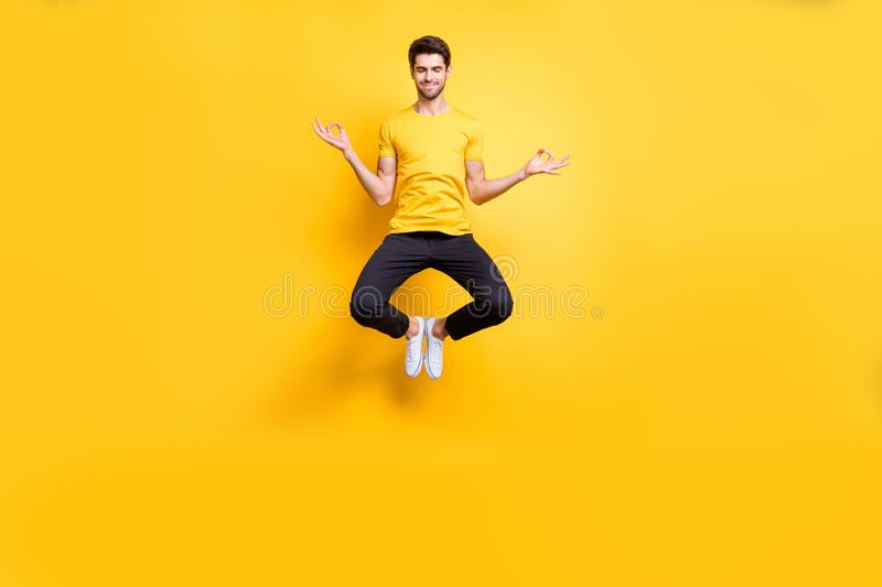 Full body photo of handsome guy jumping high lotus position morning yoga training relaxing fingers together wear casual stock image