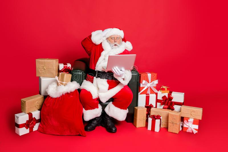 Full body photo of impressed santa claus in hat with eyewear eyeglasses read noel news on his laptop feel stupor. Full body photo of impressed santa claus in hat royalty free stock images