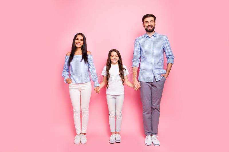 Full body photo of lovely mom dad child holding hands smiling wearing white t-shirt trousers isolated over pink royalty free stock images