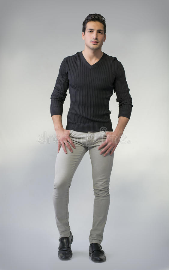 Full body photo of young man standing on grey background stock photography