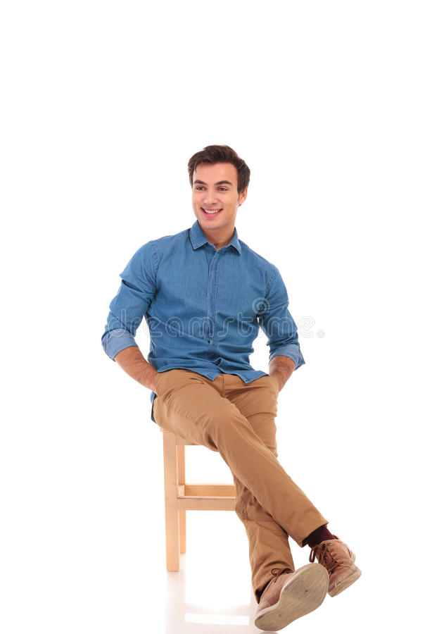 Full body picture of relaxed seated man looking to side stock image