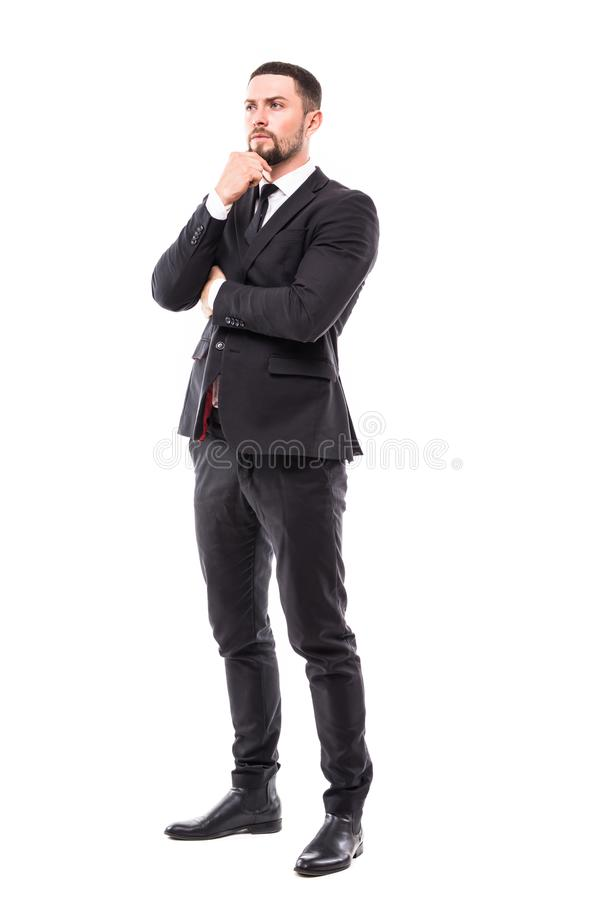 Full body picture of a smiling young business man holding his chin and thinking on white background royalty free stock photography