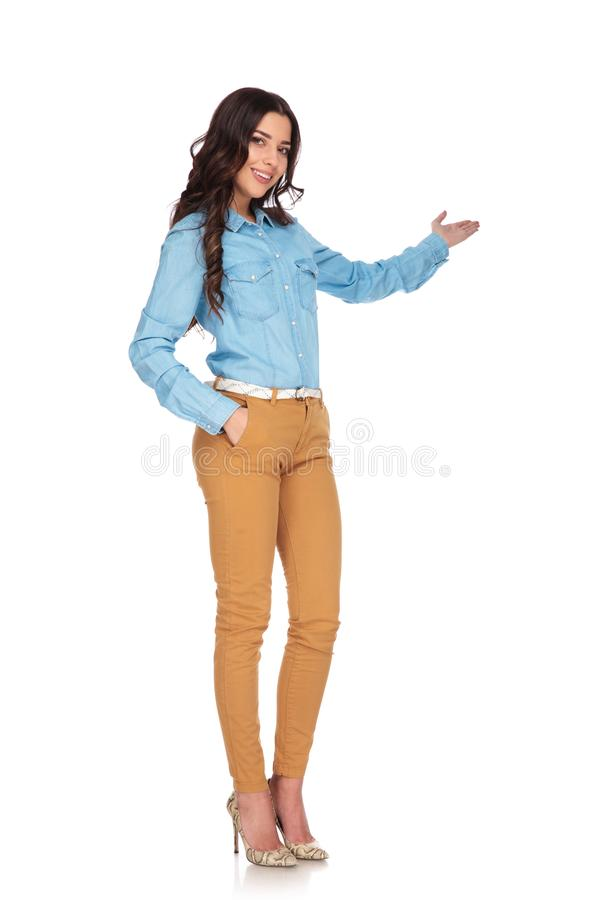 Full body picture of a young casual woman presenting royalty free stock photos
