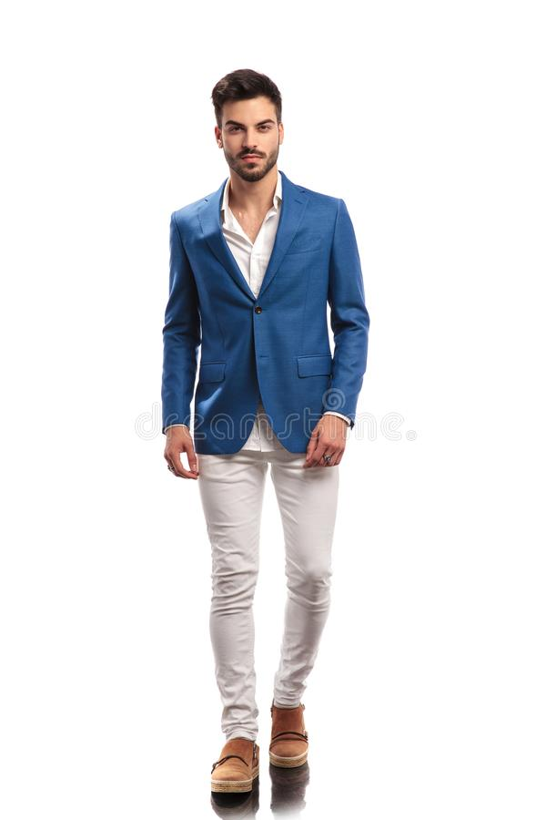 Full body picture of a young smart casual man walking stock photography