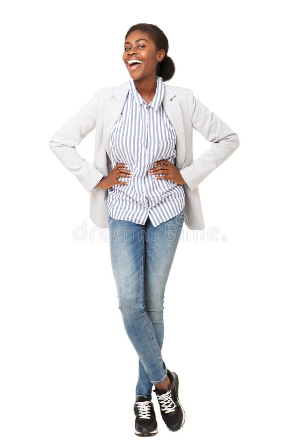 Full body attractive young black woman in blazer smiling against isolated white background stock images