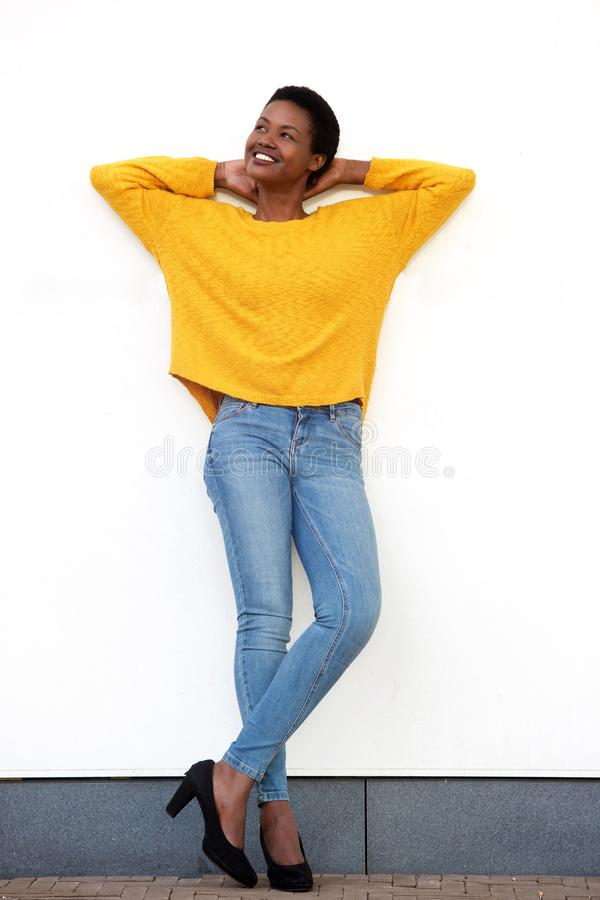 Full body beautiful young african american woman smiling against white wall with hands behind head. Full body portrait of beautiful young african american woman stock photography