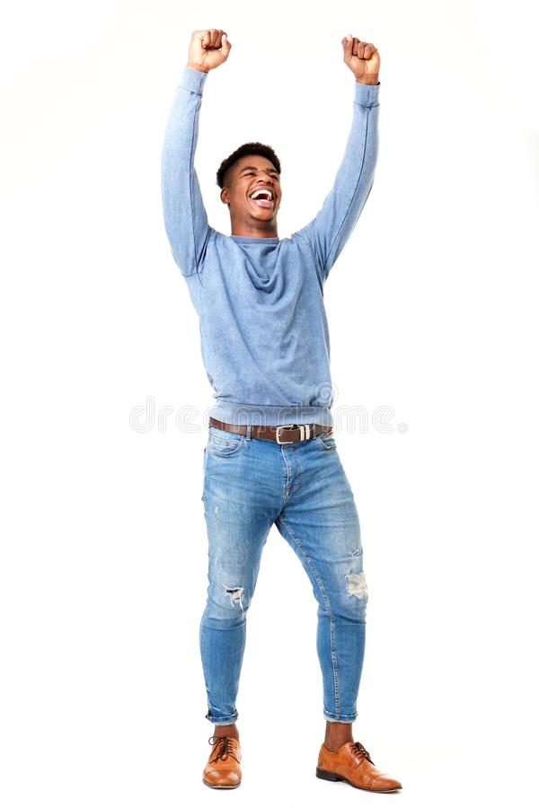 Full body cheerful young black man with arms raised against isolated white background. Full body portrait of cheerful young black man with arms raised against royalty free stock photo