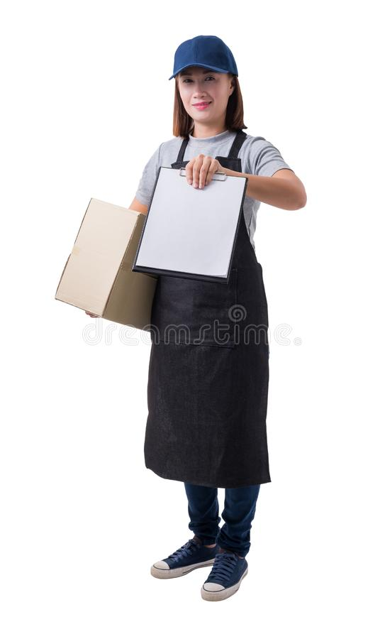 Delivery woman in Gray shirt and apron with stack of boxes is carrying parcel and presenting receiving form isolated. Full Body portrait of delivery woman in royalty free stock photography