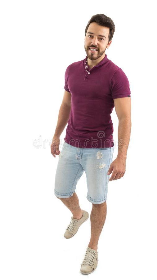 Full body portrait of friendly man walking. Beautiful and bearded person. He is wearing a magenta polo shirt and shorts jeans.. stock image