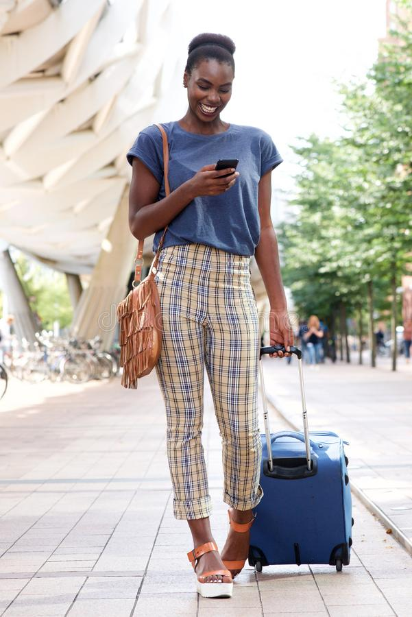 Full body happy young african american travel woman walking in city with bags and mobile phone. Full body portrait of happy young african american travel woman royalty free stock photo