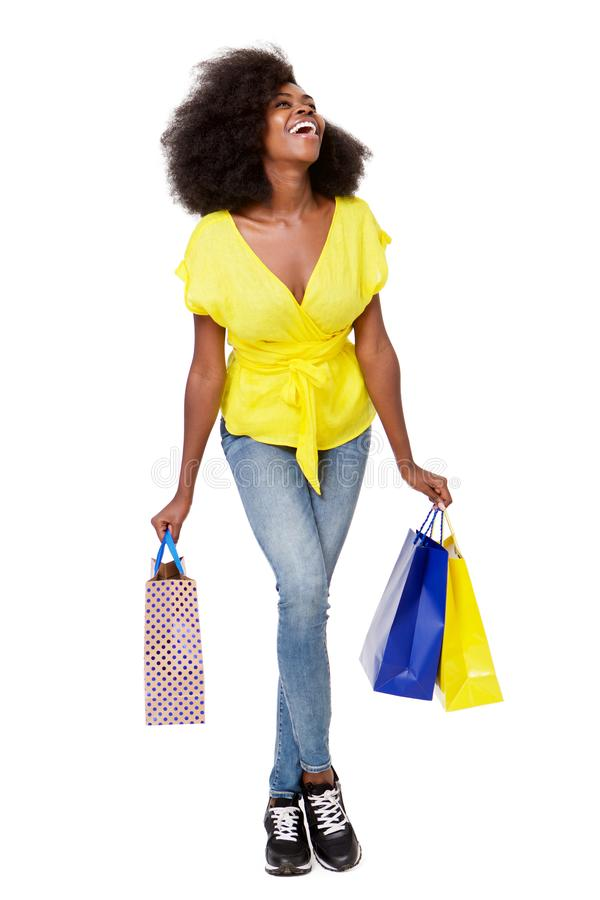 Full body portrait of happy young black woman with shopping bags royalty free stock photo