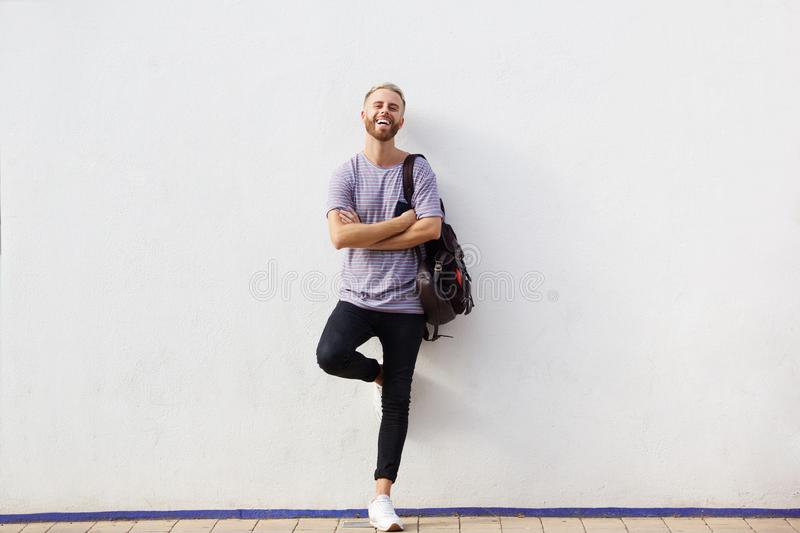 Full body happy young man with beard leaning against wall with arms crossed royalty free stock image