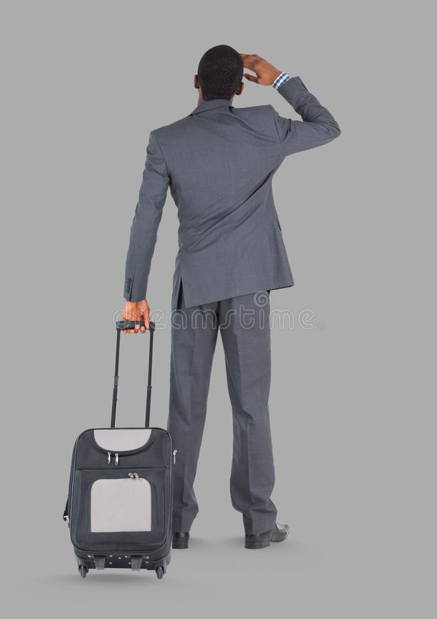 Full body portrait of man holding suitcase standing with grey background stock photo