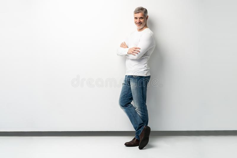 Full body portrait of relaxed mature man standing with arms crossed over white background. royalty free stock images