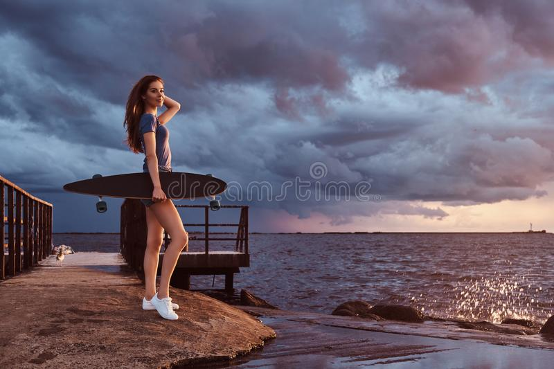 Portrait of a sensual girl holds a skateboard while standing on the beach is enjoying amazing dark cloudy weather during. Full body portrait of a sensual girl stock image