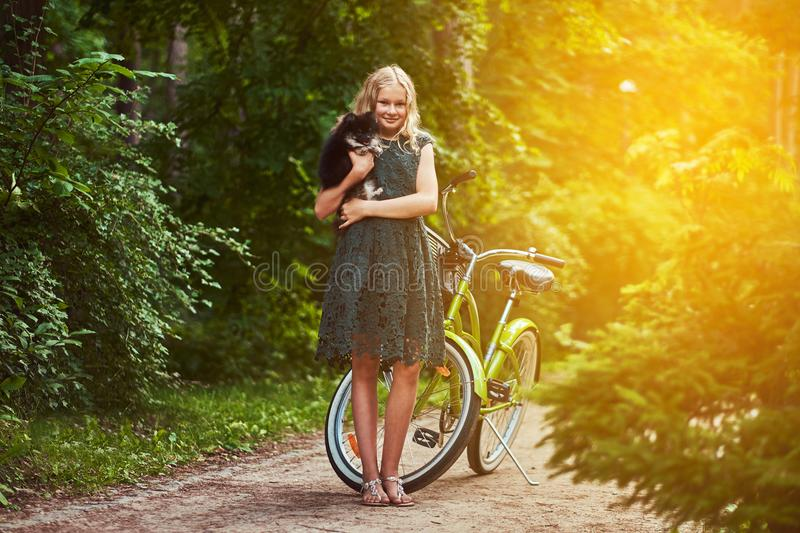Full body portrait of a smiling little blonde girl in a casual dress, holds cute spitz dog. Ride on a bicycle in the stock images