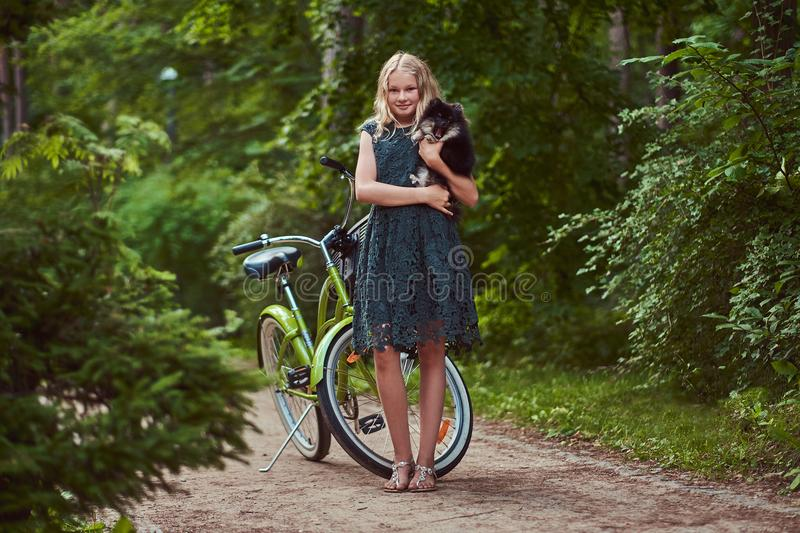 Full body portrait of a smiling little blonde girl in a casual dress, holds cute spitz dog. Ride on a bicycle in the royalty free stock photography