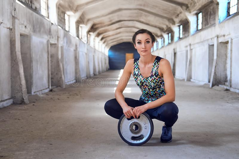 Full body portrait of the sporty female doing squats. stock photos