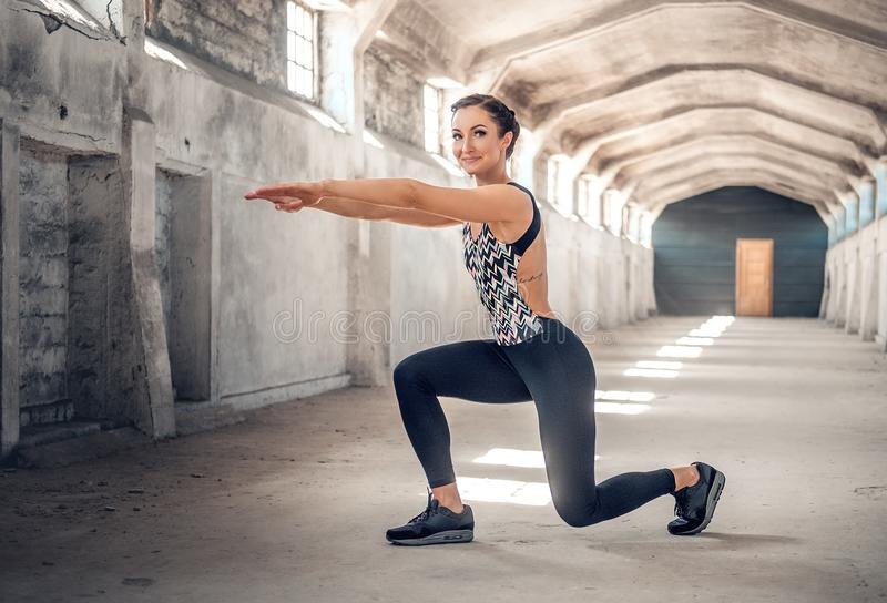 Full body portrait of the sporty female doing squats. stock image