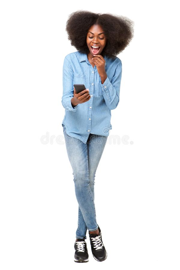 Full body surprised young woman looking at mobile phone royalty free stock image