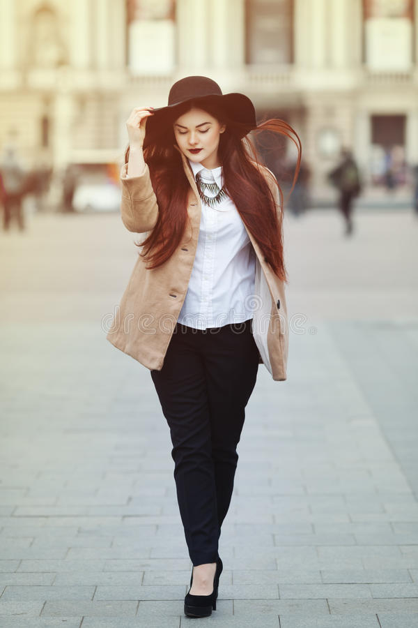 Full body portrait of young beautiful lady wearing stylish classic clothes walking at street. Girl looking down. Plus royalty free stock photo