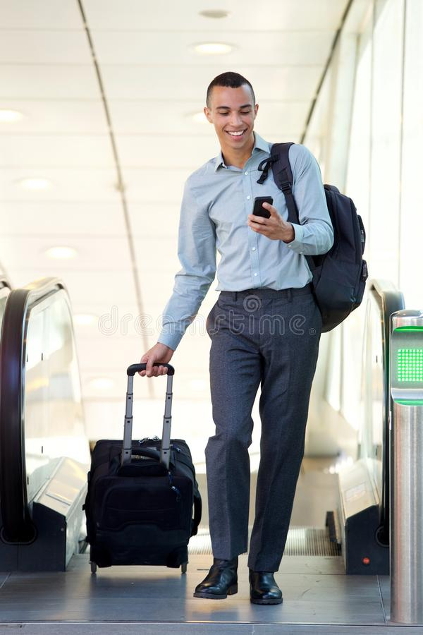 Full body young businessman walking with travel bags and mobile phone. Full body portrait of young businessman walking with travel bags and mobile phone stock photo
