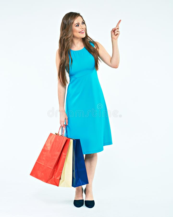 Full body portrait of young woman with shopping bag pointing fin stock photography