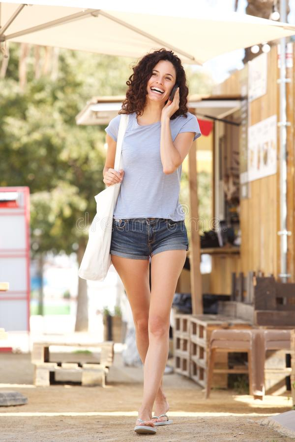 Full body young woman talking on cell phone outside in summer. Full body portrait of young woman talking on cell phone outside in summer stock photo