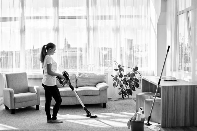 Full body portrait of young woman in white shirt and jeans cleaning carpet with vacuum cleaner in living room, copy space. stock image
