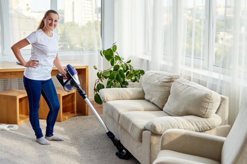 Full body portrait of young woman in white shirt and jeans cleaning carpet with vacuum cleaner in living room, copy space. royalty free stock photo