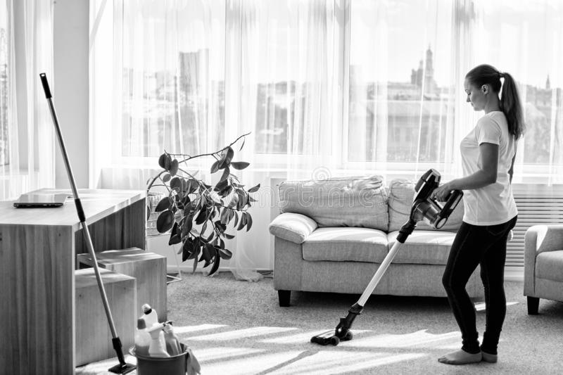 Full body portrait of young woman in white shirt and jeans cleaning carpet with vacuum cleaner in living room, copy space. royalty free stock photos