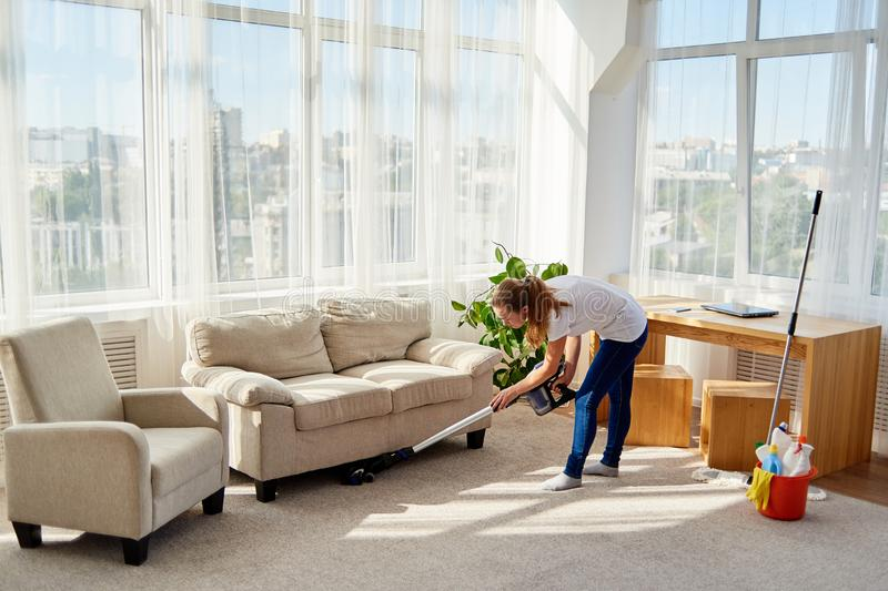 Full body portrait of young woman in white shirt and jeans cleaning carpet with vacuum cleaner in living room, copy space. royalty free stock photography