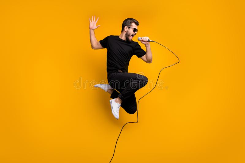Full body profile photo of crazy hipster guy jumping high holding microphone music lover singing favorite song wear sun. Full body profile photo of crazy hipster royalty free stock photo