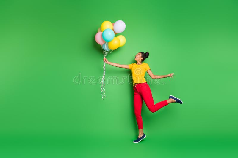 Full body profile photo of pretty millennial dark skin lady holding air balloons going to fly up in sky wear casual stock image