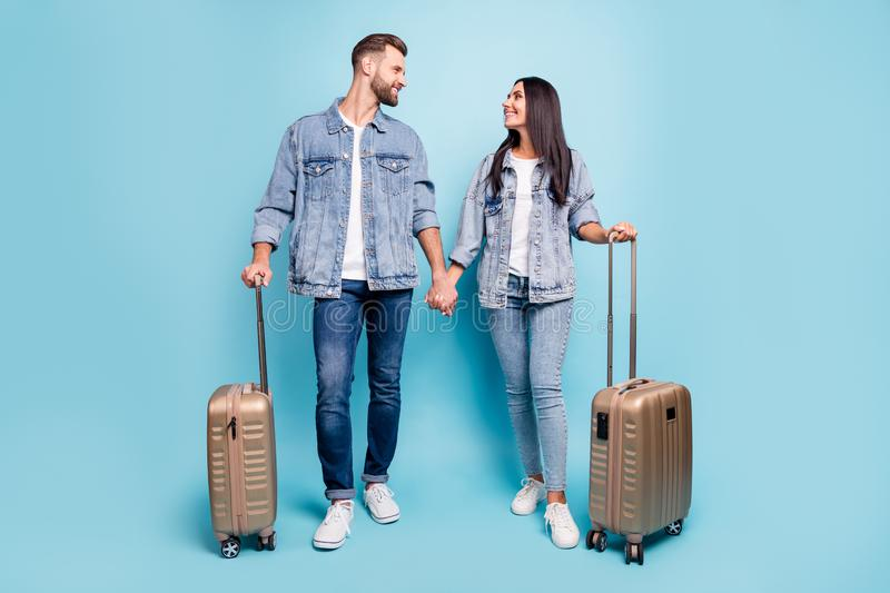 Full body profile side photo of charming holding pack looking enjoying wearing denim jeans jackets  over blue. Full body profile side photo of charming holding royalty free stock photography