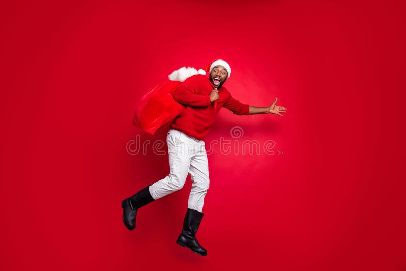 Full body profile side photo of cheerful guy in xmas santa claus hat holding carrying bag in christmas night wearing. Full body profile side photo of cheerful royalty free stock photography