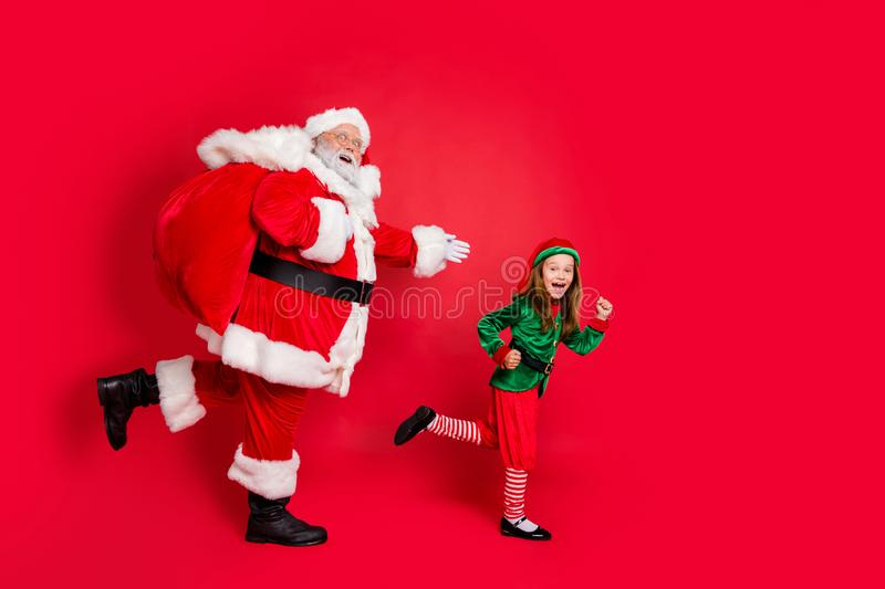 Full body profile side photo of cheerful two fairy runners santa claus elf in hat headwear carrying heavy bag with. Presents on midnight, wearing eyeglasses stock image