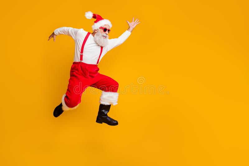 Full body profile side photo of crazy funky grey hair bearded grandfather hipster in red hat jump run enjoy x-mas time. Full body profile side photo of crazy royalty free stock photos