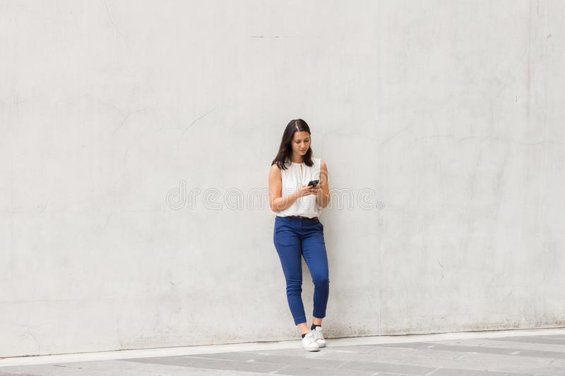 Full length shot of beautiful young woman standing and using mobile phone outdoors. Full body shot of brunette beautiful young woman standing against wall stock image