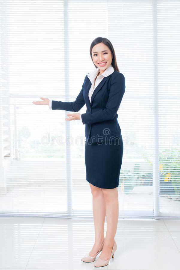 Full body shot of confident Asian businesswoman standing in office gesture hands stock image