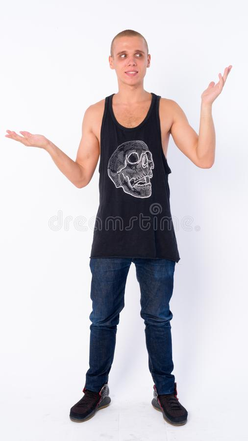 Full body shot of confused young bald rebellious man shrugging shoulders. Studio shot of young bald rebellious man isolated against white background royalty free stock photos