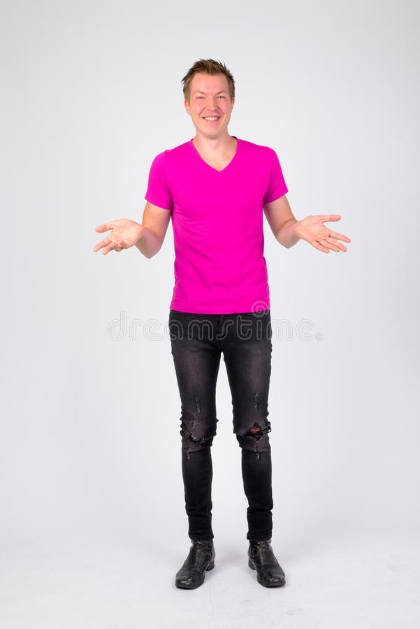 Full body shot of happy young handsome man shrugging shoulders. Studio shot of young handsome man wearing purple shirt against white background stock photos