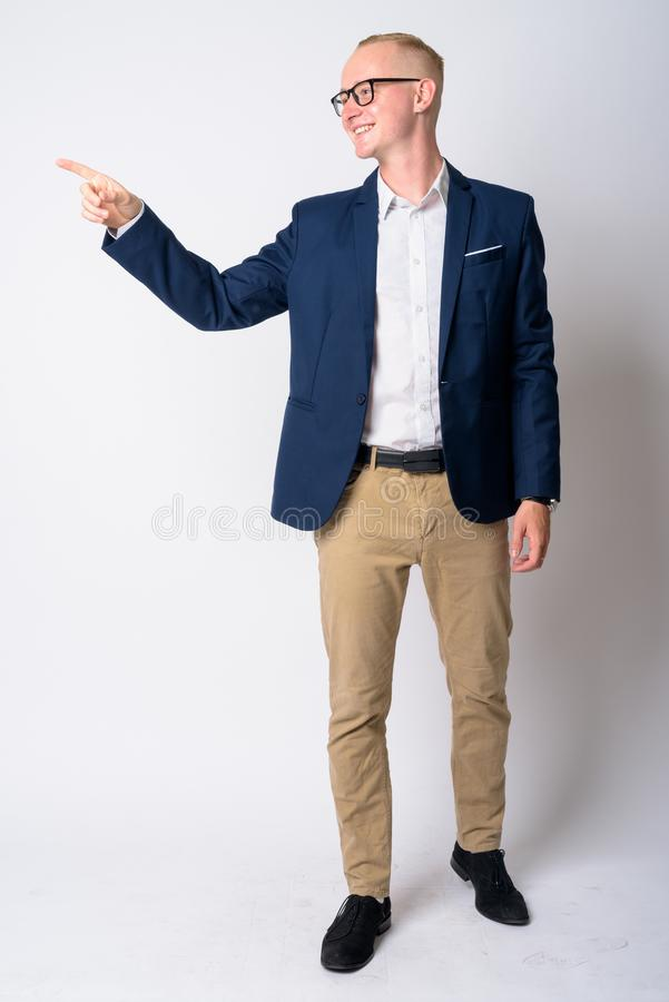 Full body shot profile view of happy young blonde businessman looking and pointing to the side royalty free stock photography