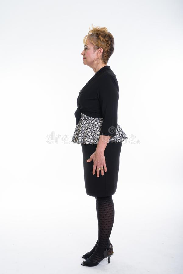 Full body shot profile view of senior Asian businesswoman standi. Ng against white background royalty free stock photo