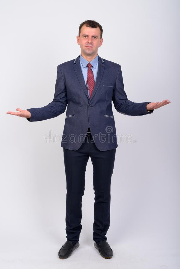 Full body shot of serious businessman in suit shrugging shoulders. Studio shot of businessman wearing suit against white background royalty free stock images