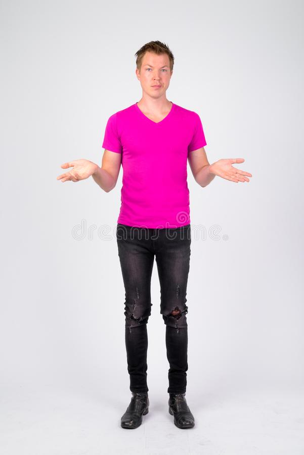 Full body shot of stressed young man shrugging shoulders. Studio shot of young handsome man wearing purple shirt against white background stock photo