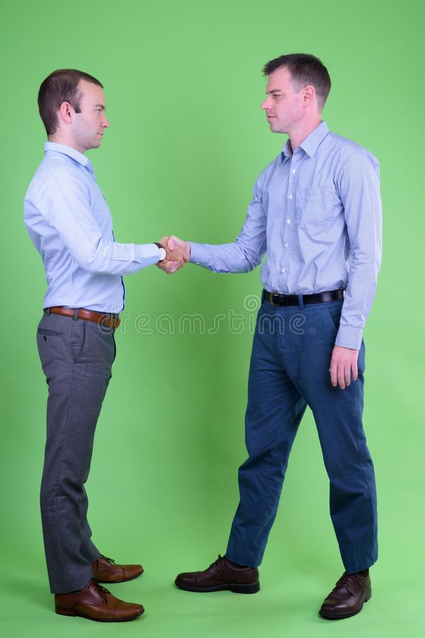 Full body shot of two businessmen shaking hands together royalty free stock photography