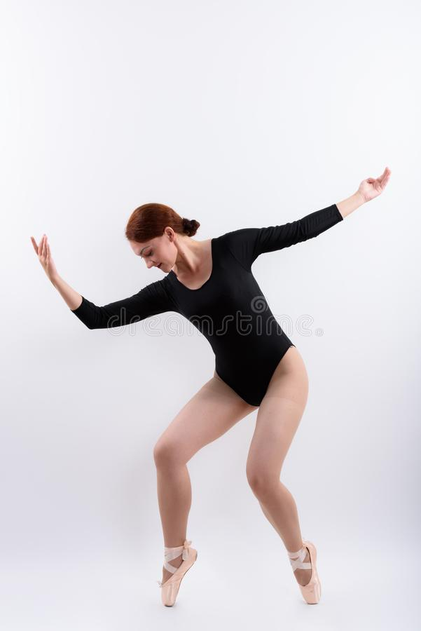 Full body shot of woman ballet dancer posing on toes. Isolated against white background royalty free stock image