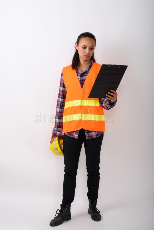 Full body shot of young Asian woman construction worker standing royalty free stock photography